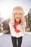 Smiling woman with red cup standing near cosy mountain house