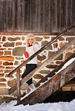 Smiling woman with cup standing on stairs of cosy mountain house