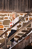 Young woman with cup standing on stairs of cosy mountain house
