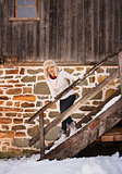 Happy woman in white sweater on stairs of cosy mountain house