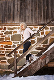 Cheerful woman in white sweater on stairs of cosy mountain house
