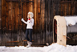Woman in furry hat holding red cup in front of rustic wood wall