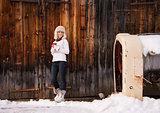 Happy woman with red cup in front of rustic wood wall