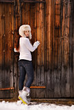 Woman in white sweater and furry hat posing near wood wall