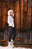 Full length portrait of woman standing near rustic wood wall