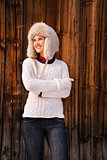 Woman in knitted sweater and furry hat standing near wood wall