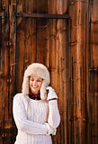 Woman in white knitted sweater standing near rustic wood wall