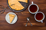 New York cheesecake on rustic wooden background with cup of tea, tongs for dessert and yellow daffodil.