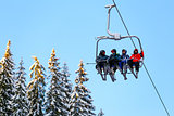 Bottom view ski family on chair lift