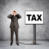 Businessman word tax on post sign