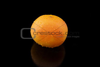 a grapefruit with drops of water on black background