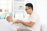 Asian father playing with baby