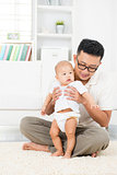 Asian father and baby playing at home.