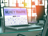 Money Traffic on Laptop in Modern Workplace Background.