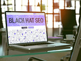 Black Hat SEO on Laptop in Modern Workplace Background.