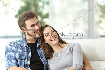 Couple at home thinking and looking sideways