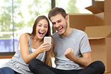 Euphoric couple moving house and watching phone