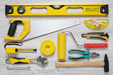 Top view of construction instruments and tools on wooden DIY workbench. Level, saw, glasses, tape measure, wrench, spanner,paint roll, hammer, cutter, pliers.