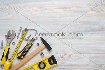 Top view of construction instruments and tools on wooden DIY workbench. with open space. Level, tape measure, wrench, hammer, cutter.