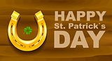 Happy St Patricks Day. Golden Horseshoe and quatrefoil clover on wooden board. Template greeting card