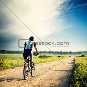 Cyclist Riding a Bike on the Country Road