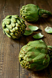 raw artichokes on a wooden surface