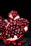 Fresh pomegranate and seeds on black