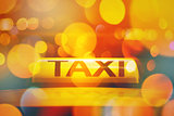 Taxi sign on vehicle rooftop with city bokeh light
