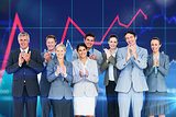 Composite image of smiling business team applauding at camera