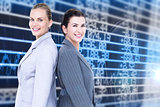 Composite image of attractive businesswomen standing back-to-back