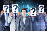 Composite image of business colleagues hiding their face with question mark sign