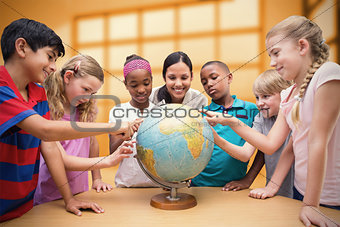 Composite image of cute pupils and teacher looking at globe in library