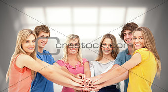 Composite image of friends standing around each other as they stack their hands