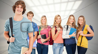Composite image of a man standing in front of his friends as he smiles
