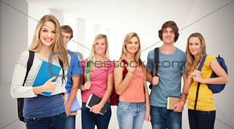 Composite image of a smiling girl standing in front of her friends