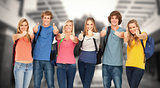Composite image of smiling group giving a thumbs up as they wear backpacks