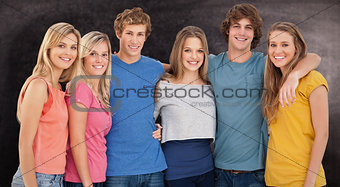 Composite image of a group of friends smiling and holding each other