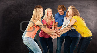 Composite image of group of friends about to cheer with their hands stacked