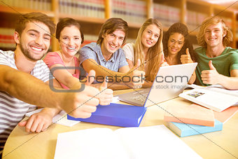 Composite image of college students gesturing thumbs up in library