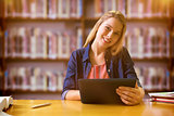 Composite image of student studying in the library with tablet
