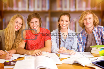 Composite image of college students doing homework in library