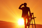 Composite image of silhouette standing on ladder