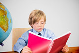 Composite image of cute pupil reading at desk