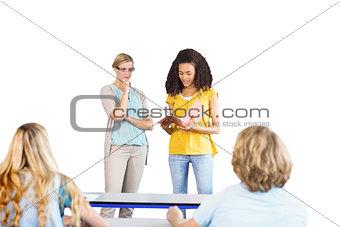 Student explaining notes besides teacher in class