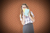 Composite image of geeky hipster hiding her face behind notepad