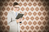 Composite image of geeky businessman reading black book