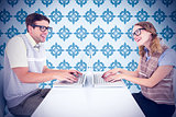 Composite image of geeky hipster couple using laptop