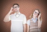 Composite image of geeky hipster couple thinking with hand on temple