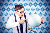 Composite image of geeky businessman pointing to globe