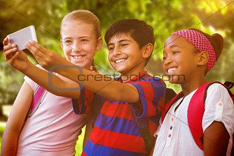 Composite image of happy kids taking selfie in school corridor